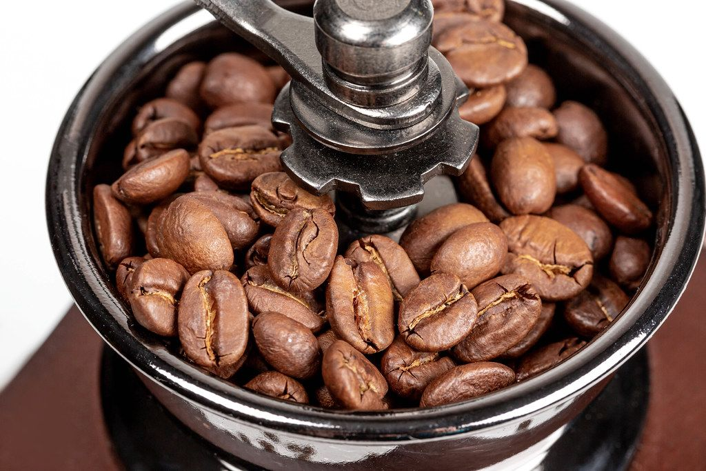 Roasted coffee beans in a mechanical coffee grinder, close-up