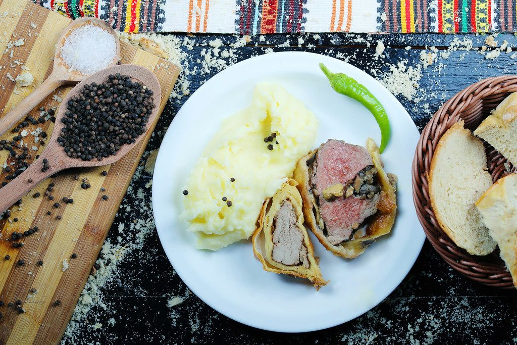Roasted pork neck with mashed potatoes served with white bread. Black background