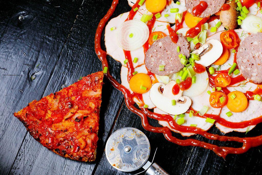 Rohe Pizzazutaten neben einem gebackenen Pizzastück und einem Pizzaschneider