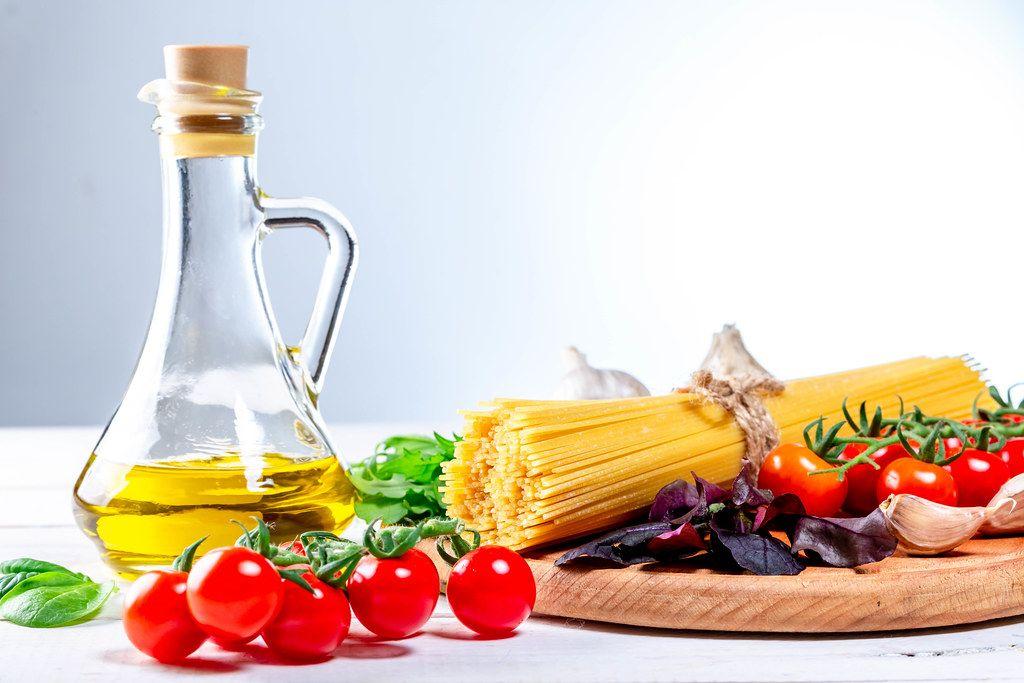 Rohe Spaghetti mit Kräutern, Tomaten, Knoblauchzehe und Olivenöl