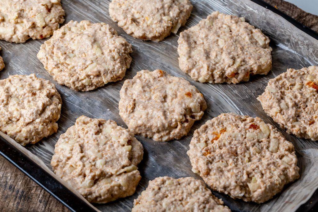 Roher Teig von Haferflocken-Keksen auf einem Backblech mit Backpapier