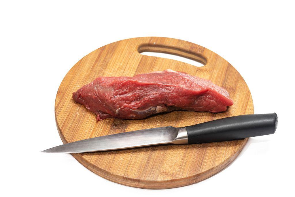 Rohes, mageres Stück Rindfleisch ungekocht liegt mit Fleischmesser auf Küchenbrett