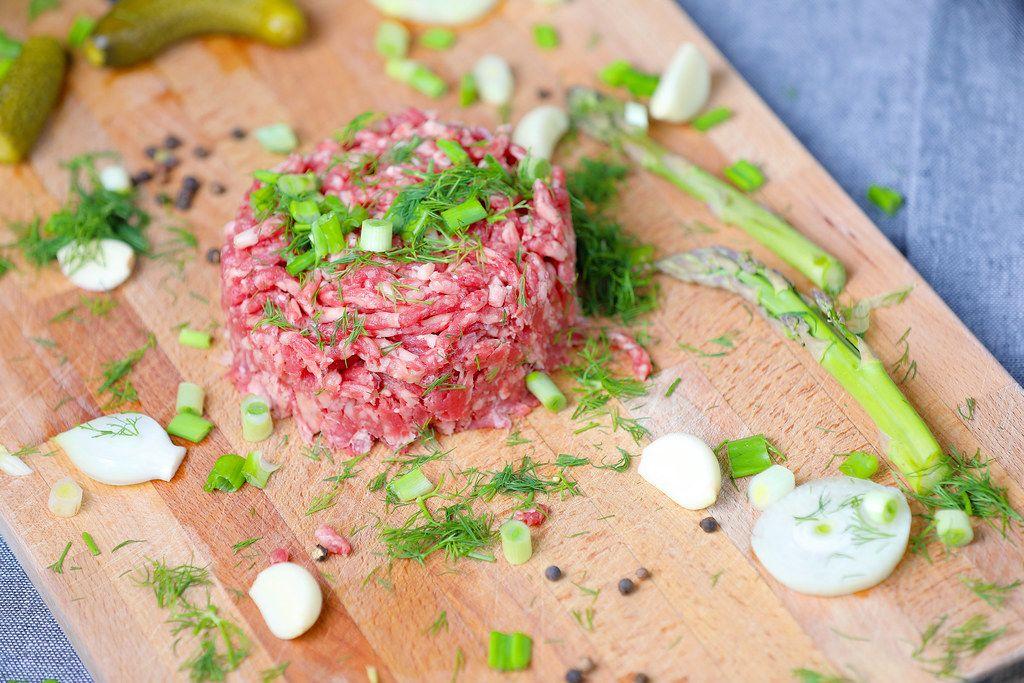 Rohes Rindfleisch: Zutaten für ein Beefsteak Tartare auf einem Holzbrettchen