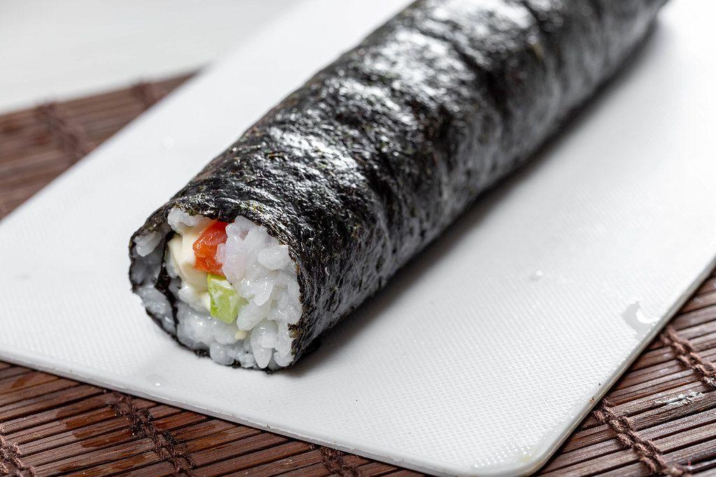 Rolling sushi maki. Preparation of Maki rolls with salmon (Flip 2019)