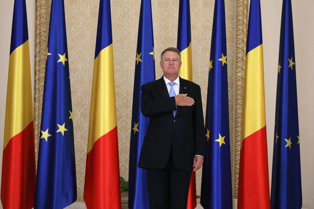 Romanian President Klaus Iohannis, flag of Romania and European Union on background