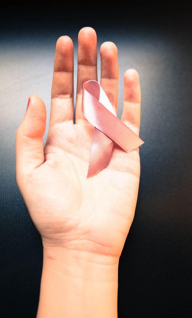 Rosa Schleife gegen Brustkrebserkrankung in der Hand einer Frau auf schwarzem Hintergrund