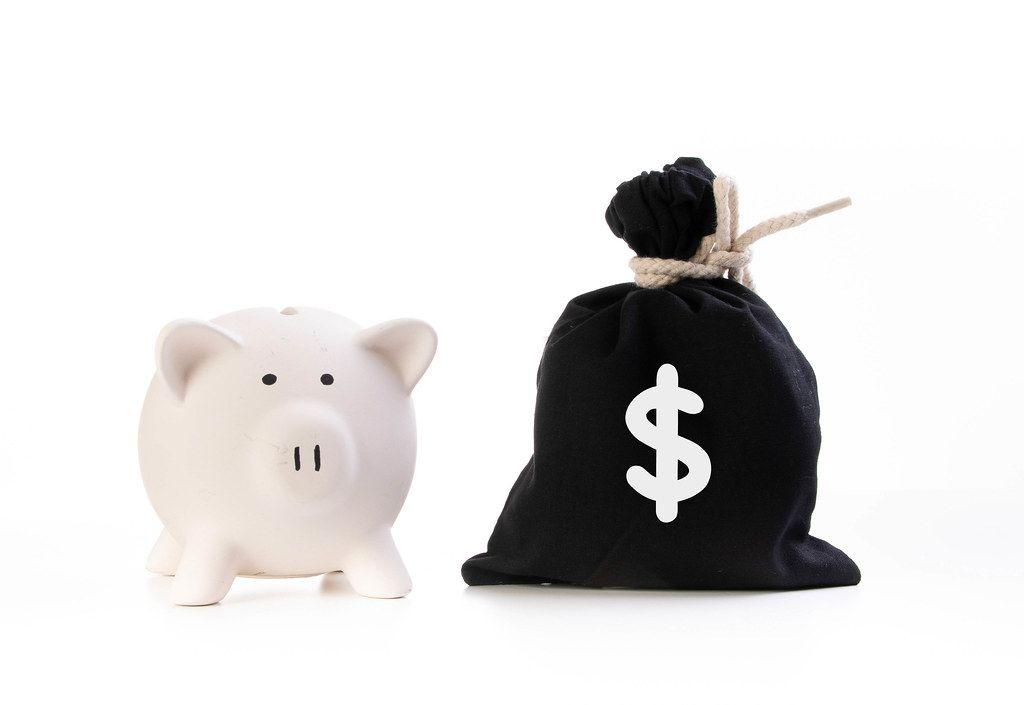Rosa Sparschwein neben einem zugeknotetem schwarzen Geldsack und dem Aufdruck eines Dollarzeichen