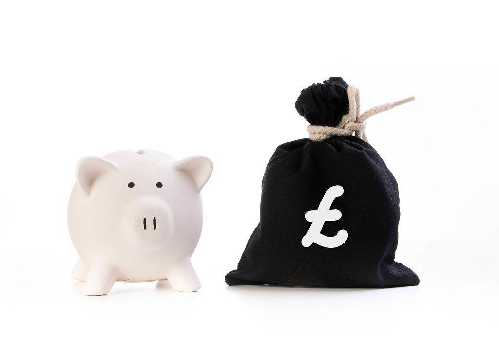 Rosa Sparschwein neben einem zugeknotetem schwarzen Geldsack und dem Britischen Pound-Symbol