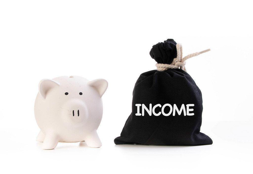 Rosa Sparschwein neben einem zugeknotetem schwarzen Geldsack und der Aufschrift Einkommen