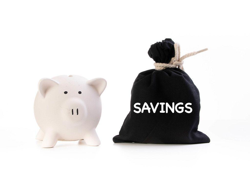 Rosa Sparschwein neben einem zugeknotetem schwarzen Geldsack und der Aufschrift Ersparnisse