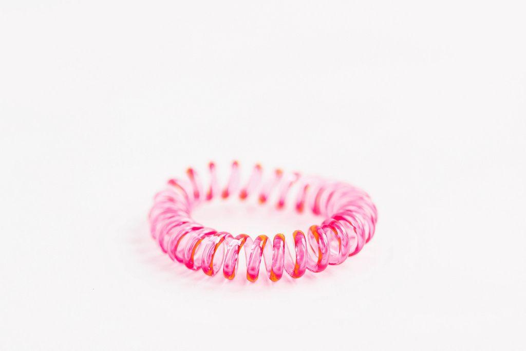 Rosafarbener Haarband aus Gummi vor weißem Hintergrund