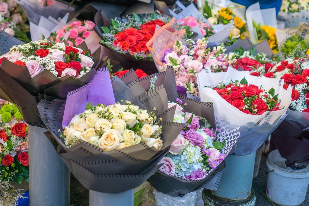 Rosensträuße mit roten, weißen und rosaroten Blumen in Vasen auf einem Straßenmarkt in Vietnam