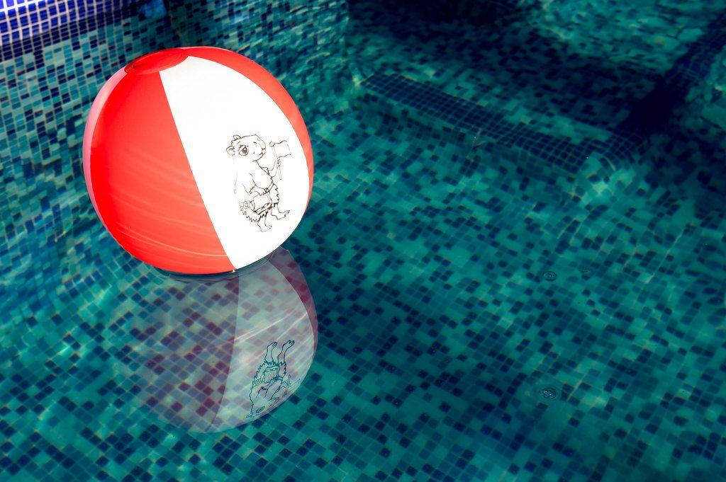 Rot-weißer Strandball im Schwimmbecken