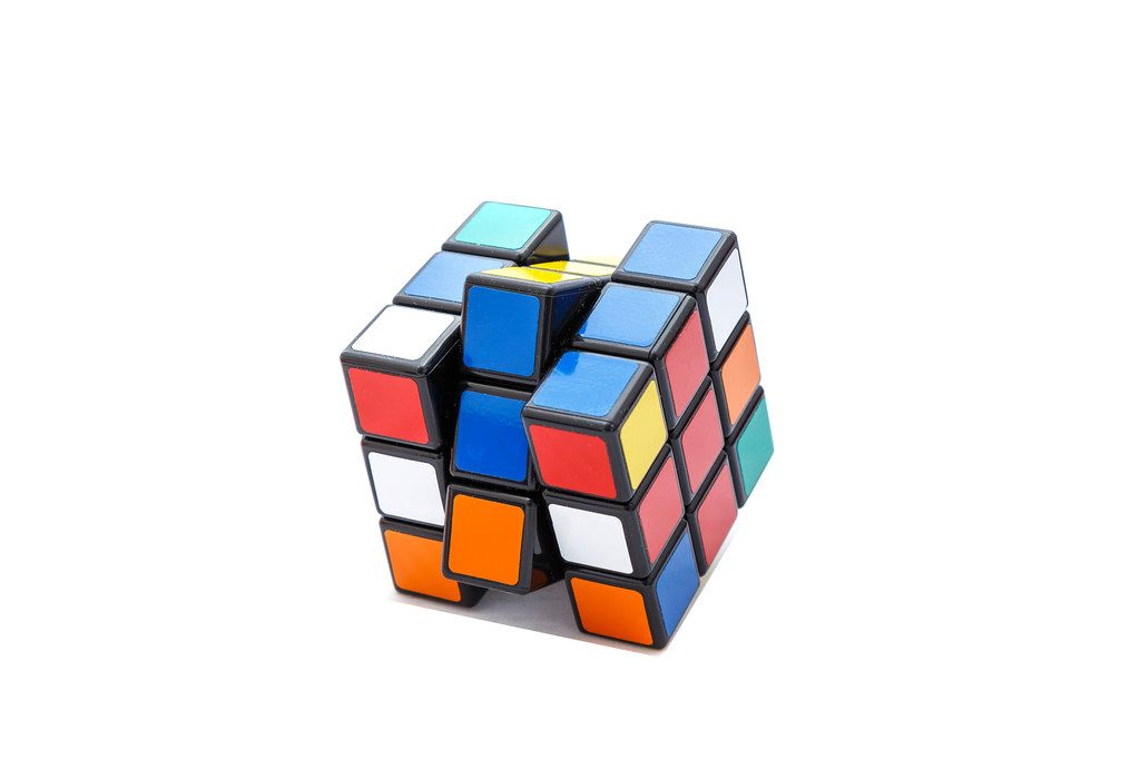 Rotated Rubik's cube 3x3x3 on white background with red and blue lines