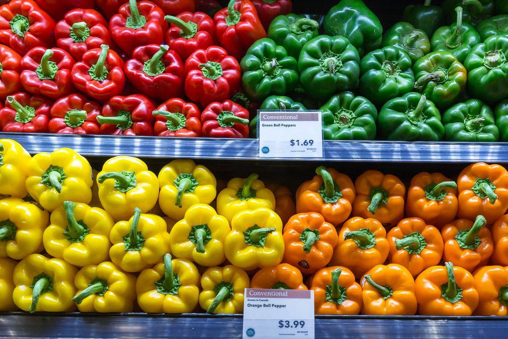 Rote, grüne, gelbe und orangefarbene Paprikas im Whole Foods Market