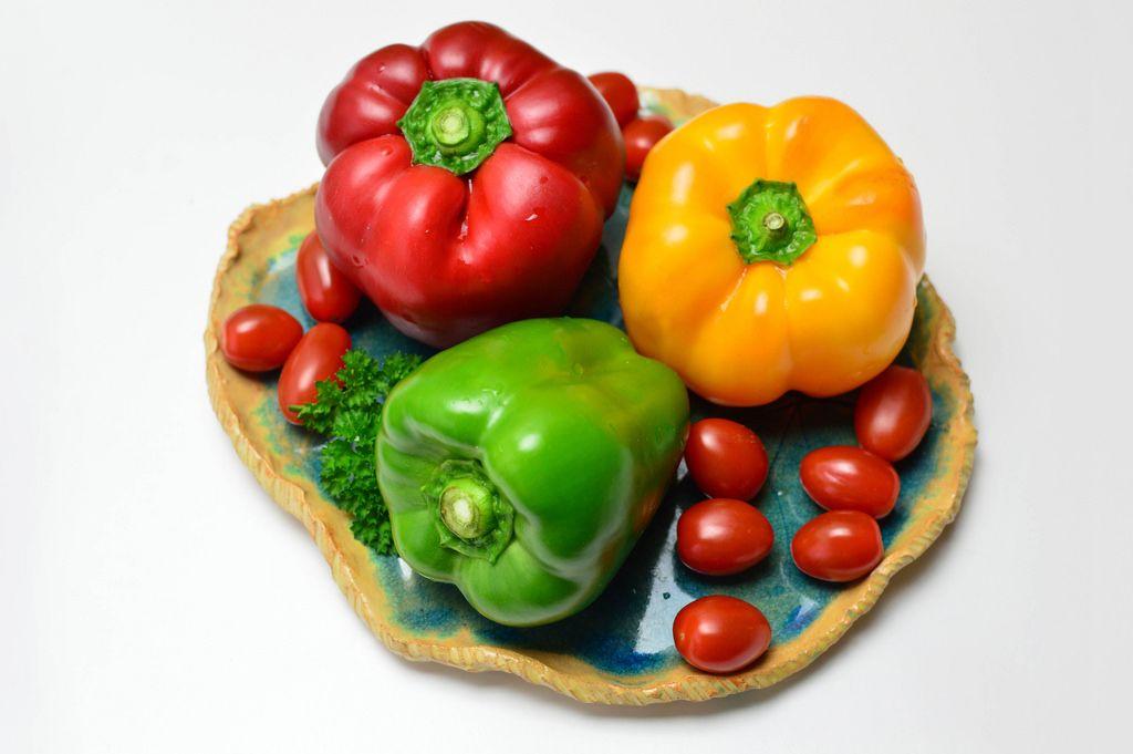 Rote, grüne und gelbe Paprika mit Kirschtomaten und Petersilie auf Tonteller