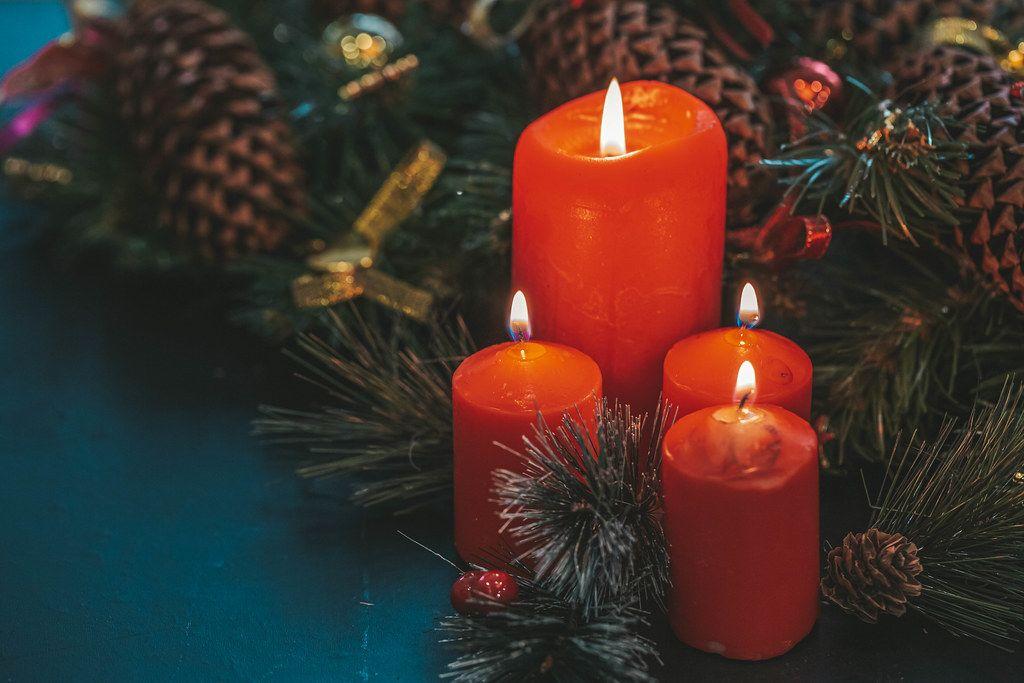 Rote Kerzen neben Tannenzweigen zur festlichen Weihnachtszeit auf schwarzem Hintergrund