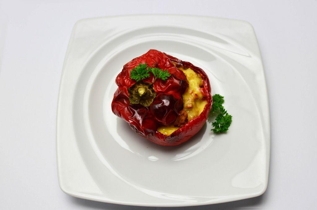 Rote Paprika mit Schweinefleisch und Käse gefüllt auf einem Teller in der Aufsicht