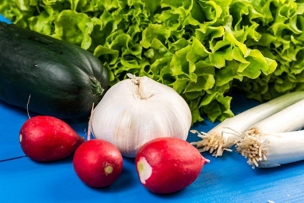 Rote Radieschen, Knoblauch, Gurke und Lauchzwiebeln vor Salatblättern auf blauem Holztisch