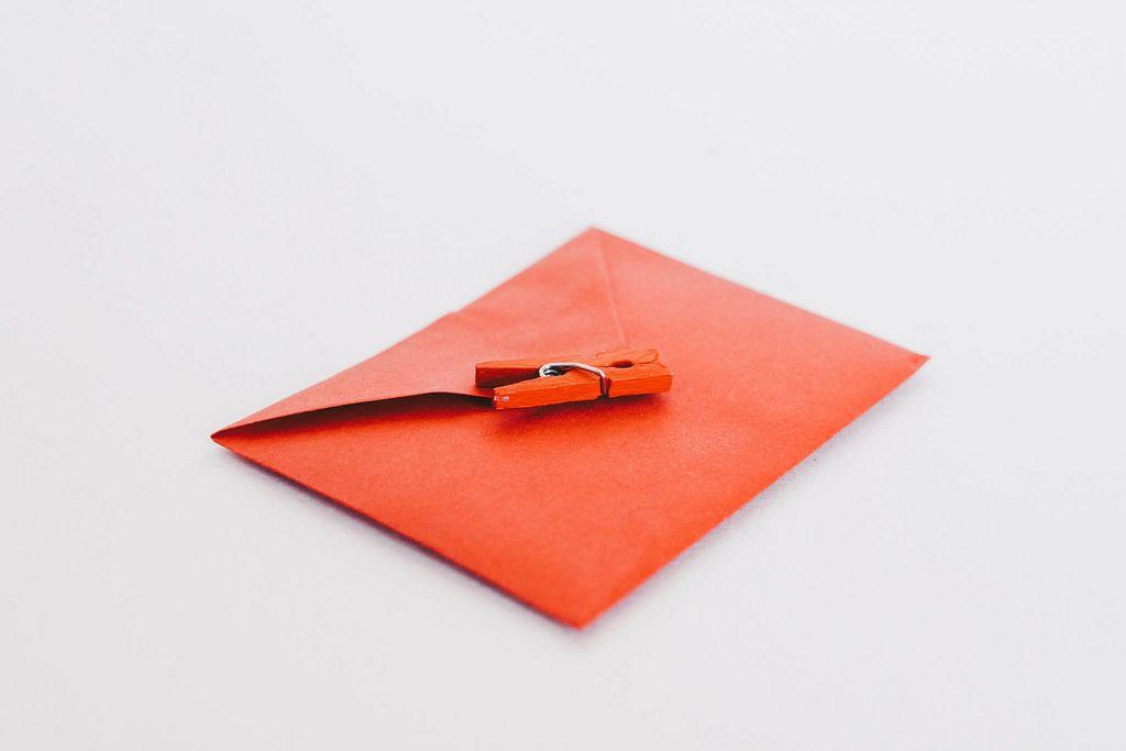 Roter Briefumschlag und rote Wäscheklammer vor weißem Hintergrund