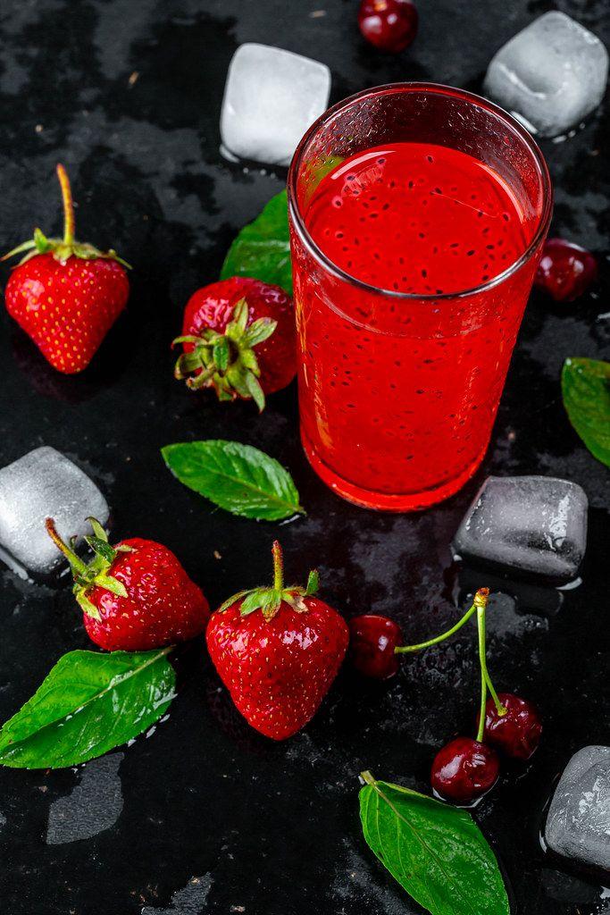 Roter Cocktail zwischen frischen Erdbeeren, Kirschen, Minzblättern und Eiswürfel, auf einem schwarzen Untergrund