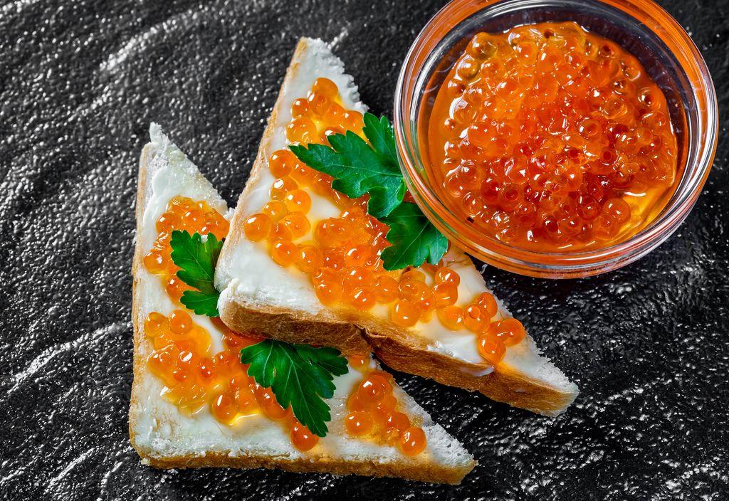 Roter Kaviar in einer Glasschüssel und auf Sandwichen auf einem schwarzen Steinhintergrund