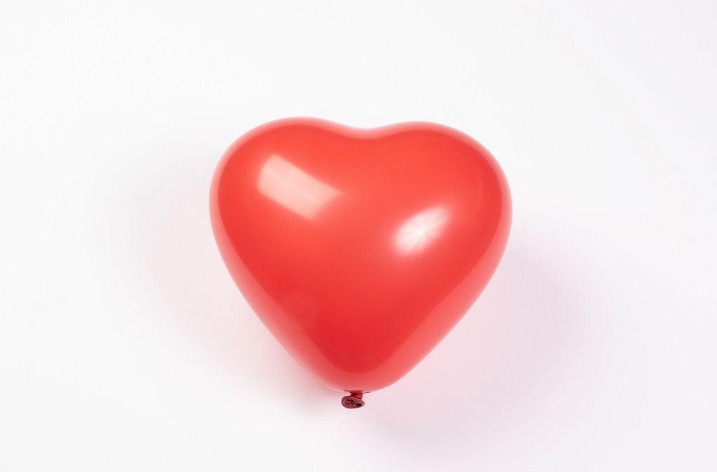 Roter Luftballon in Herzform isoliert vor weißem Hintergrund