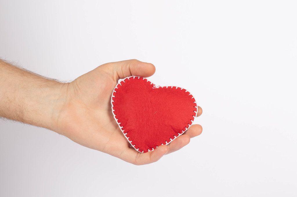 Rotes Herz in einer Hand, vor weißem Hintergrund