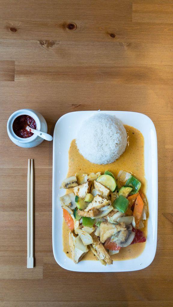 Rotes Thai-Curry mit veganen Tofu-Ecken, Zucchini, Pilzen, Paprika und Karotten auf einem Teller mit Reis, Essstäbchen und einem Gefäß mit Sambal Oelek auf einem Tisch in der Aufsicht