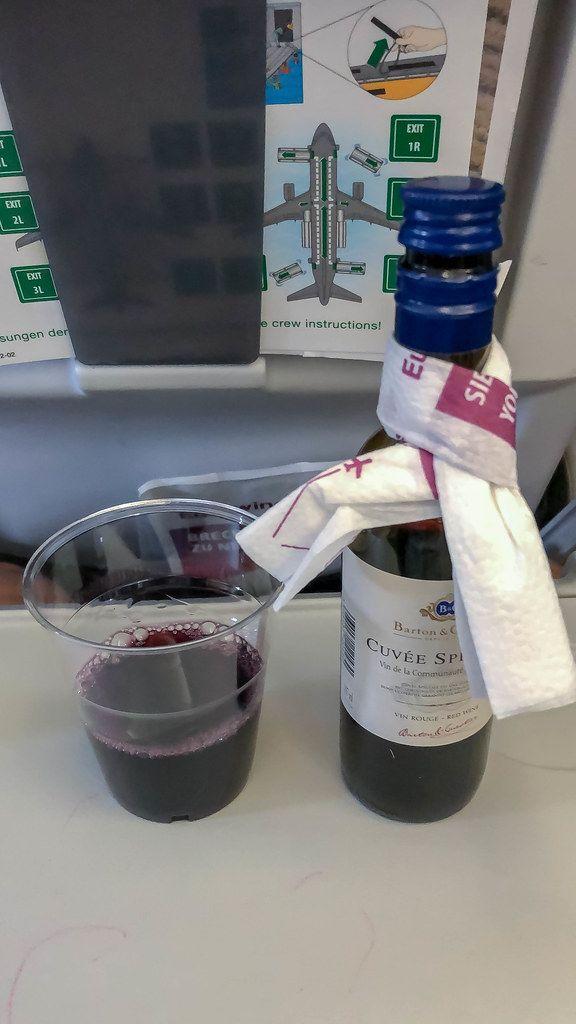 Rotwein wird mit Plastikbecher im Flugzeug auf der Flugreise als Drink serviert