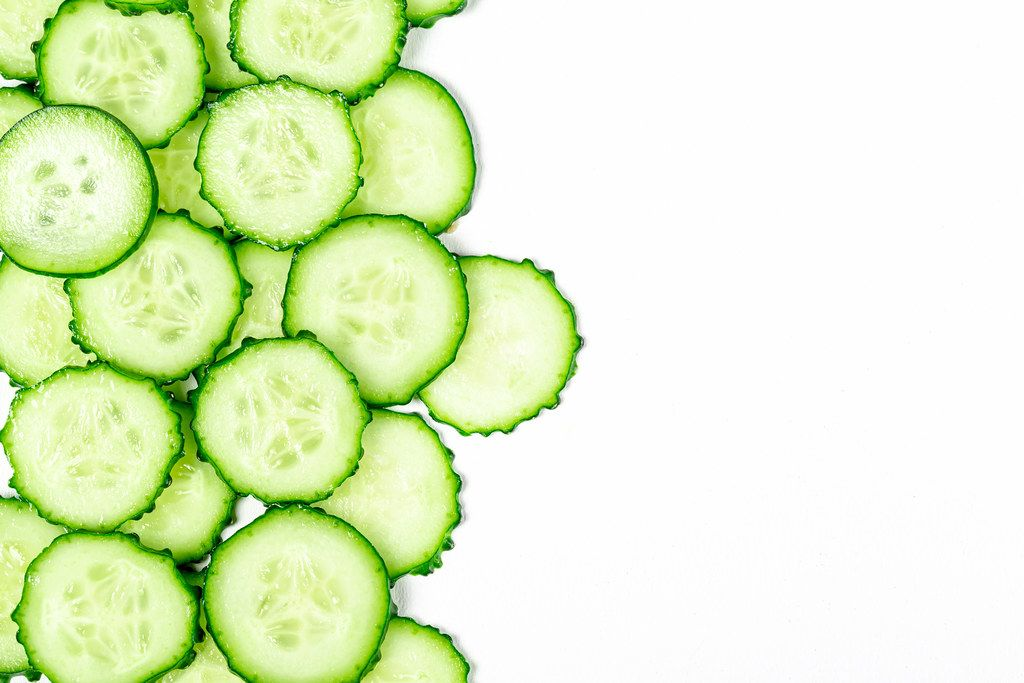 Round cucumber slices on a white background with free space