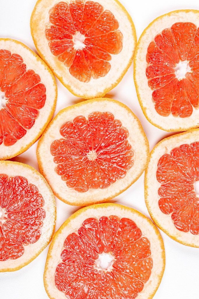 Round pieces of fresh grapefruit on a white background, top view (Flip 2020)