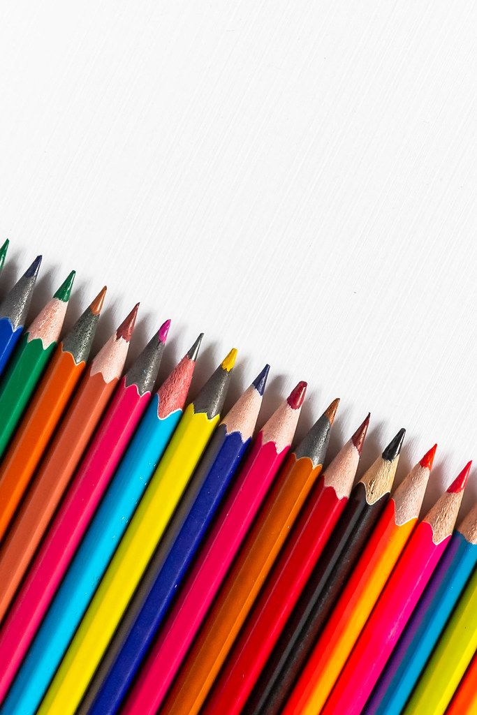 Row of colored pencils on white background