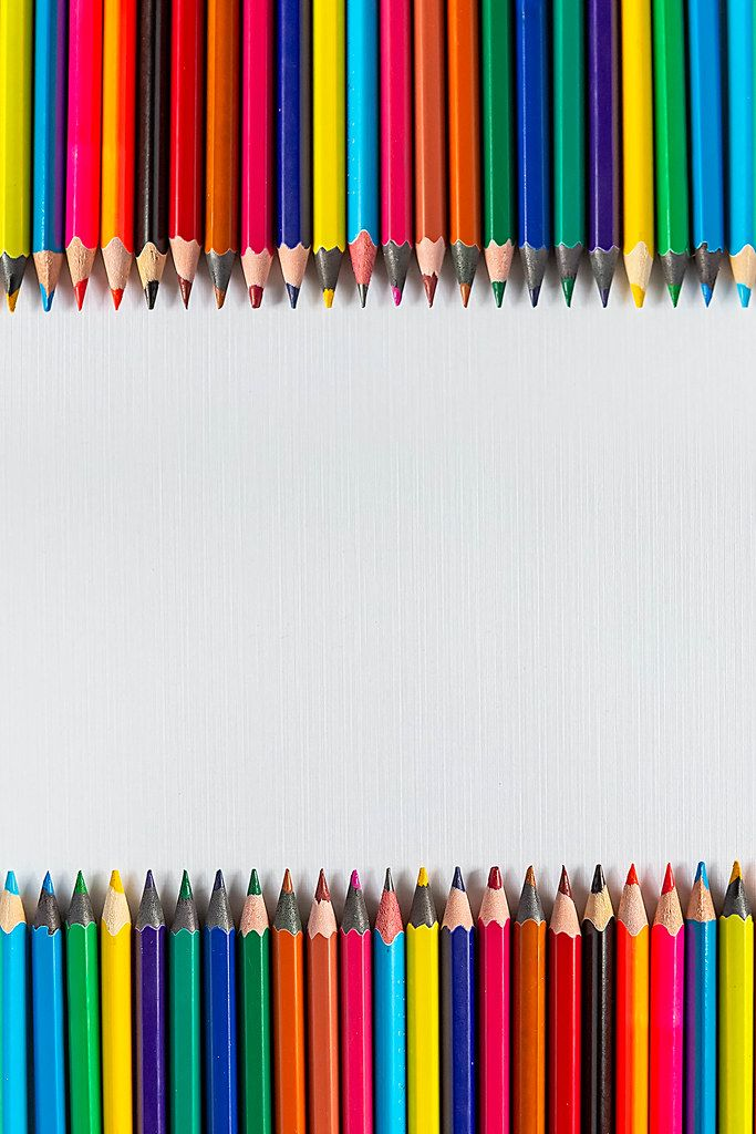 Rows of color pencils on a blank white paper
