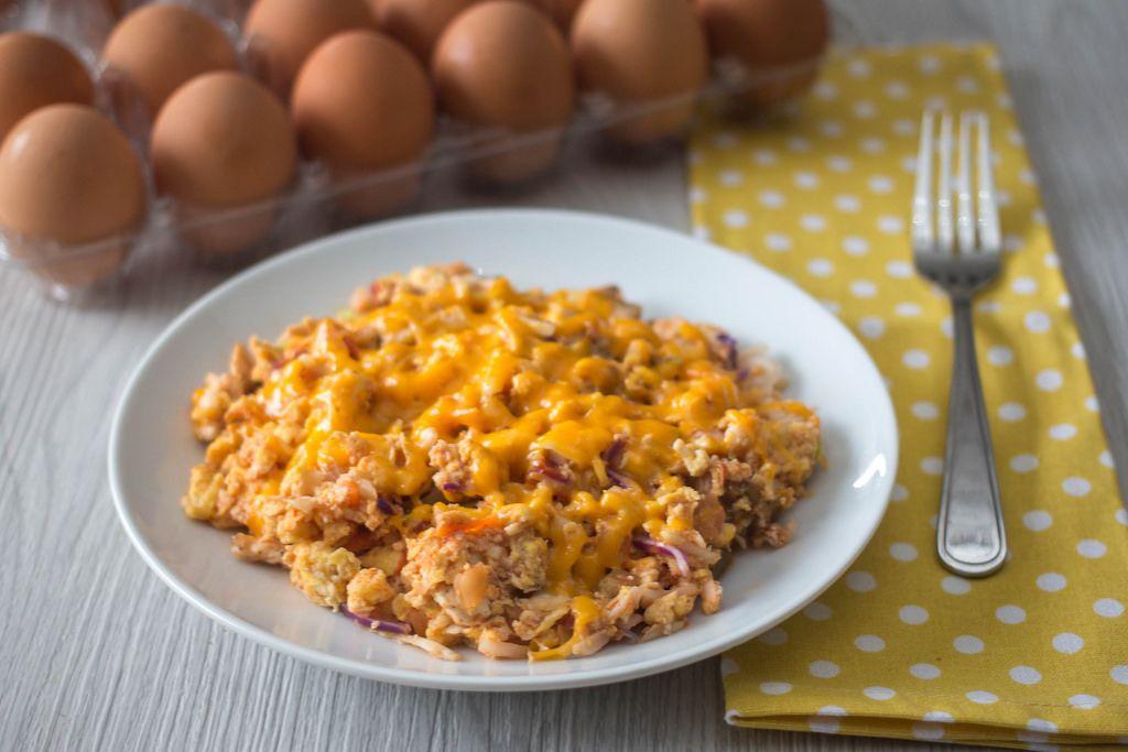 Rührei mit roten Zwiebeln und Käse auf einem Teller mit Gabel und Eier im Hintergrund