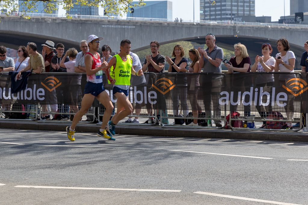 Runners running side by side and holding red rope in hands - London Marathon 2018
