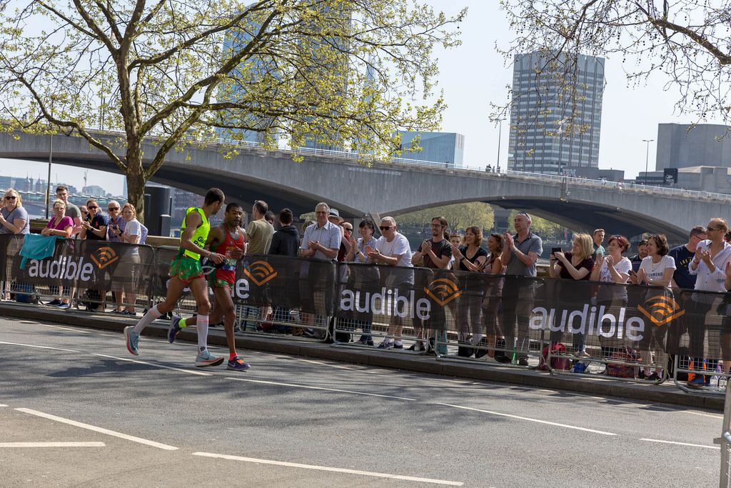 Runners running side by side and holding rope in hands - London Marathon 2018