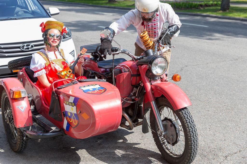 Russisches Pärchen in Tracht gekleidet fährt in einem Motorrad mit Beiwagen