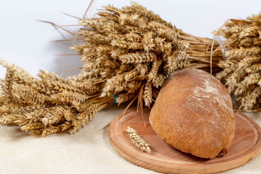 Ryebread with ears of wheat on white background