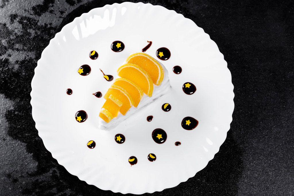Sahniges Marmeladen-Kuchen Dessert mit Schokosauce und gelben Sternen verziert, vor schwarzem Hintergrund