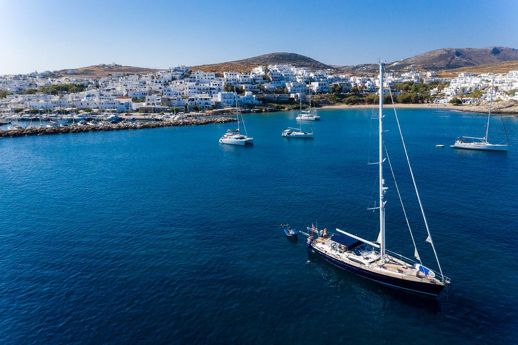 Sailboats and catamarans in the blue Aegean Sea water of bay Ormos Naousia, with typical greek houses in the background of Paros Island
