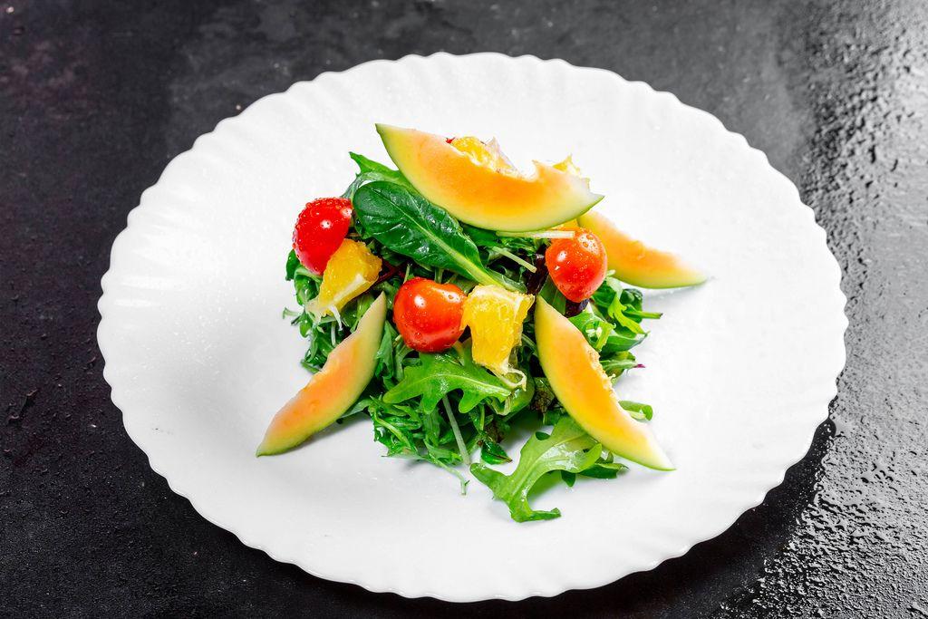 Salad with fresh avocado, cherry tomatoes, orange slices and arugula leaves (Flip 2019)