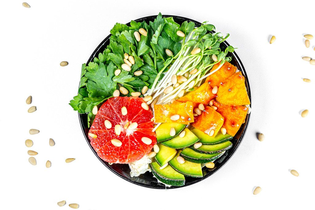 Salad with grapefruit, avocado, micro greenery and pine nuts on a white background. Top view