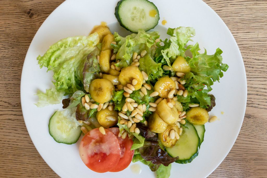 Salad with iceberg lettuce, tomato, cucumber, flambéed banana and pine nuts