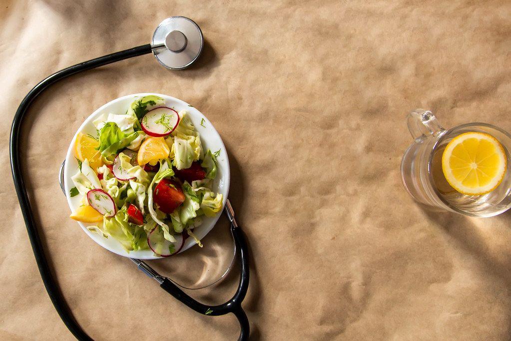 Salat aus frischem Gemüse mit Stethoskop und frischem Zitronenwasser als gesundes Ernährungskonzept