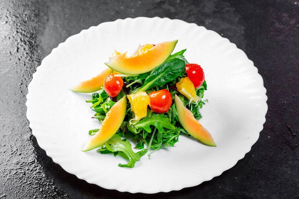 Salat mit frischen Avocadoscheiben, Kirschtomaten und Orangenstückchen und Arugola-Blätter