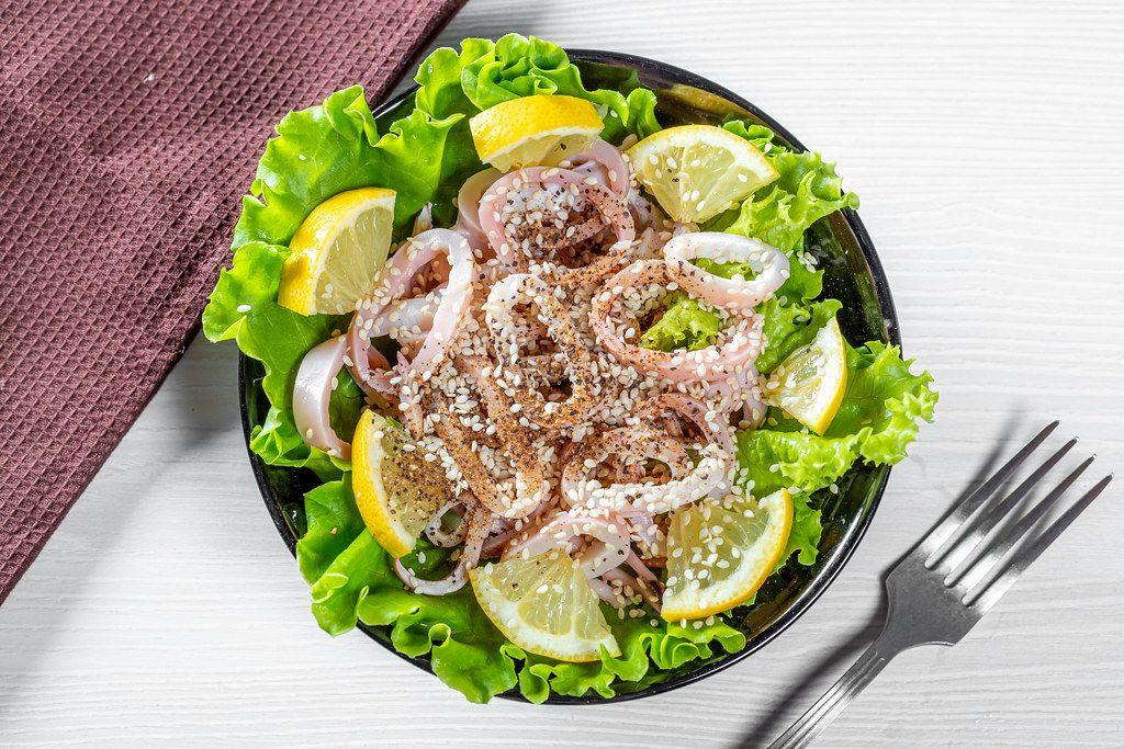 Salat mit Tinoenfischringen, Zitrone und Sesamkörnern, neben einer Gabel auf einem Küchentisch