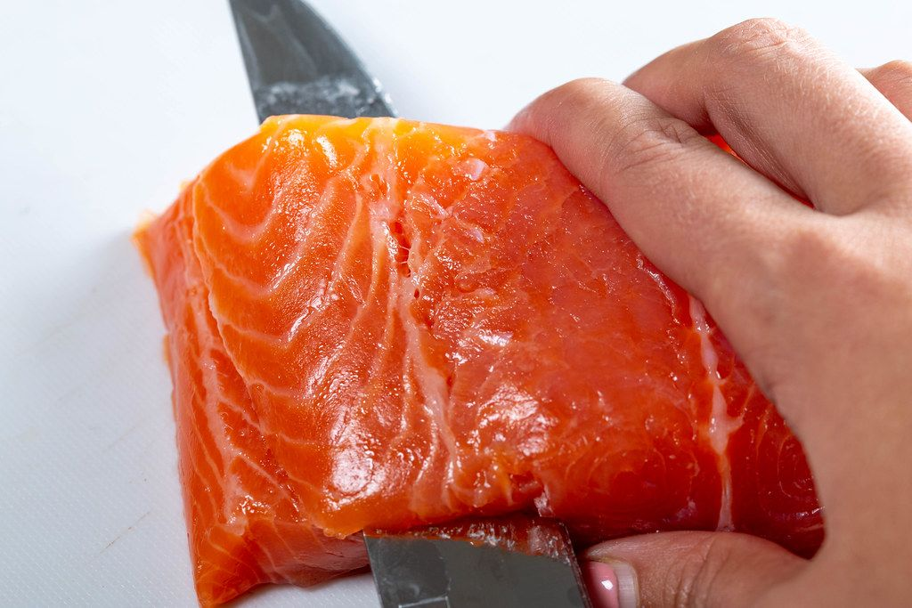 Salmon fillet is cut with a knife. Close up (Flip 2019)