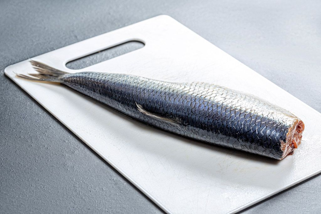 Salted herring on a white kitchen Board