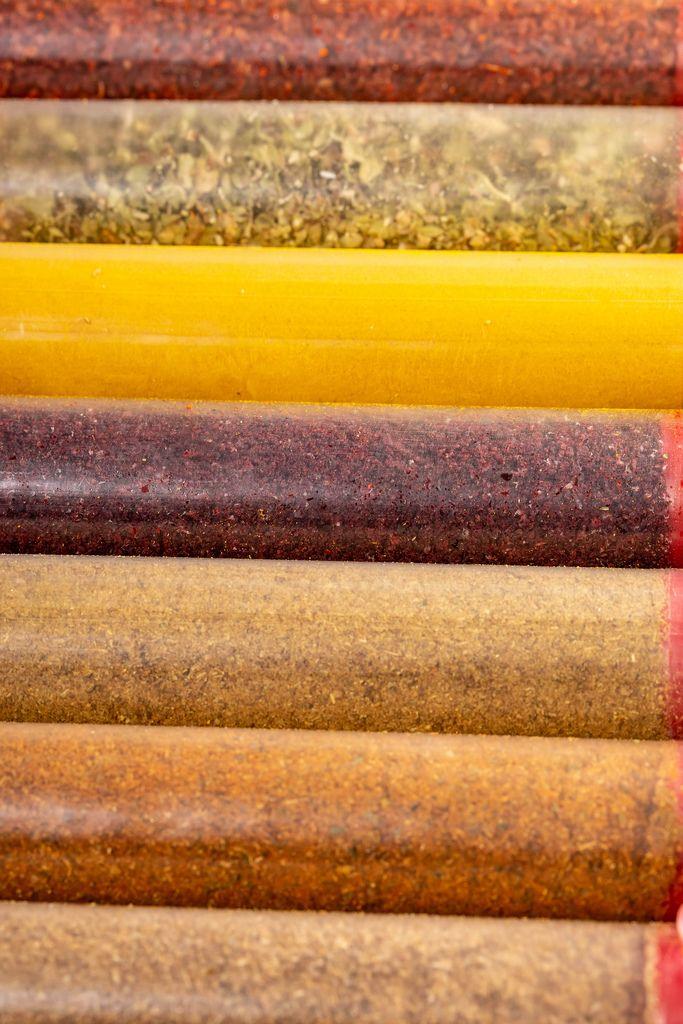 Sammlung von bunten Gewürzen und Kräutern als Hintergrundbild